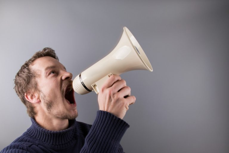Man with a white megaphone screaming