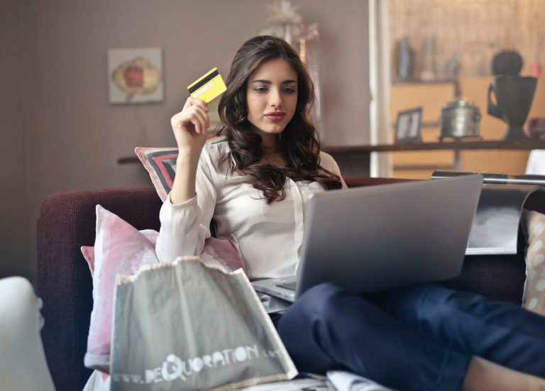 Woman holding yellow credit card in front of her laptop