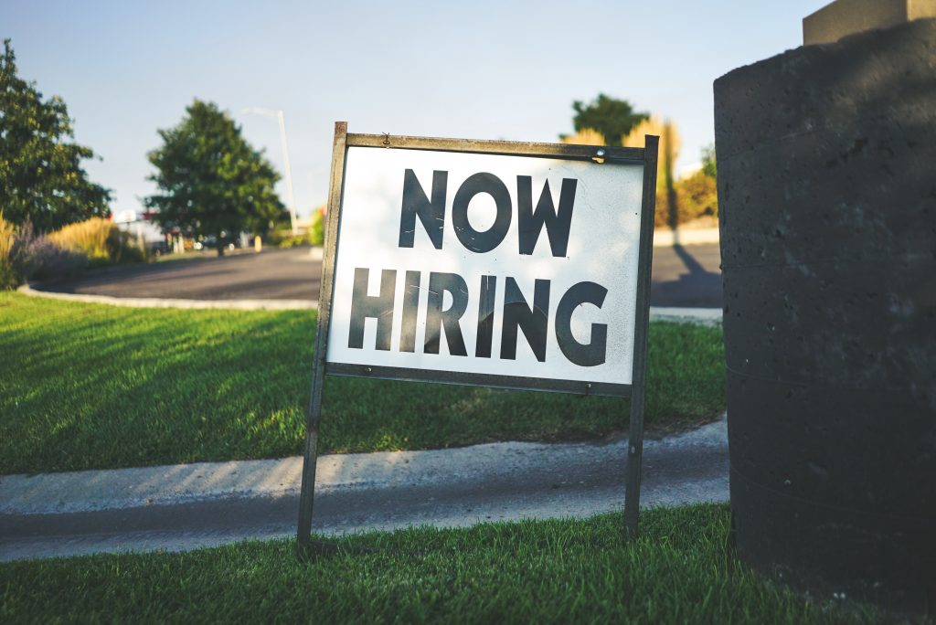 Human resources Now Hiring sign grass