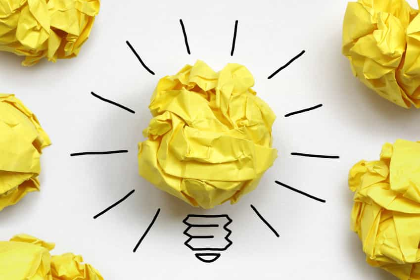Yellow scrunched up paper of discarded content writing idea surrounded by lightbulb drawing.