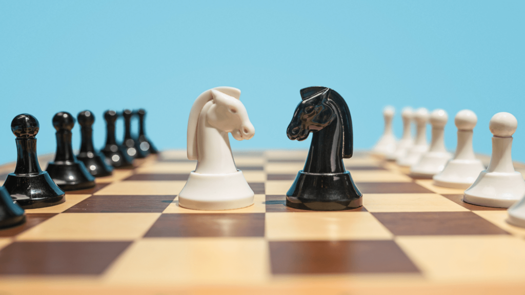 2 chess pieces face each other on chess board
