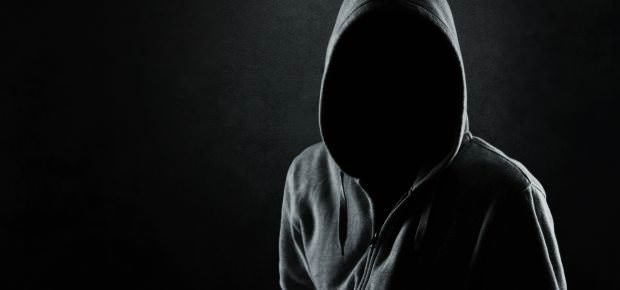 A person in a black hoodie with an indiscernible face. The face is completely dark. The background is black.