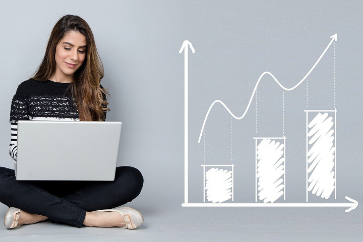 A girls sits looking at her laptop screen. To her right, an inforgraphic representation of a bar chart with a line implying increasing metrics