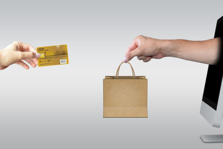 a mans arm comes out of a computer screen holding a shopping bag. another hand hold out a credit card in exchange.