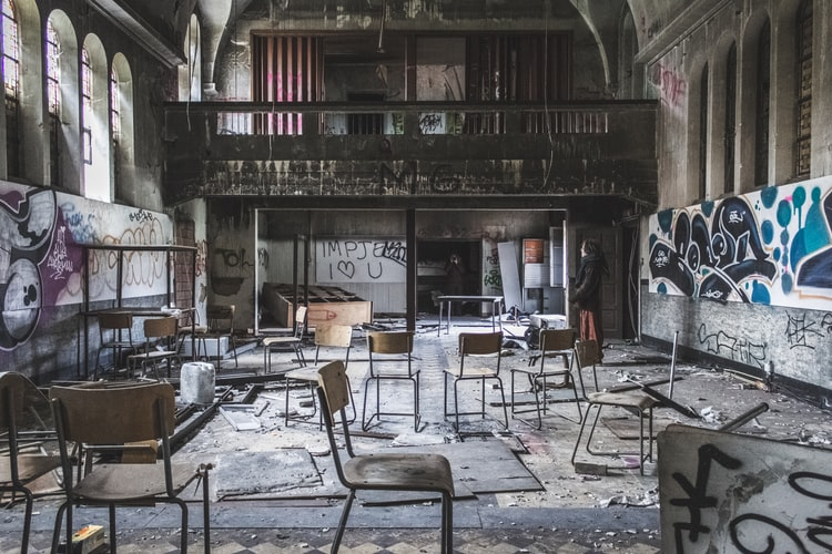 An abandoned grey classroom covered in graffiti and full of empty chairs.