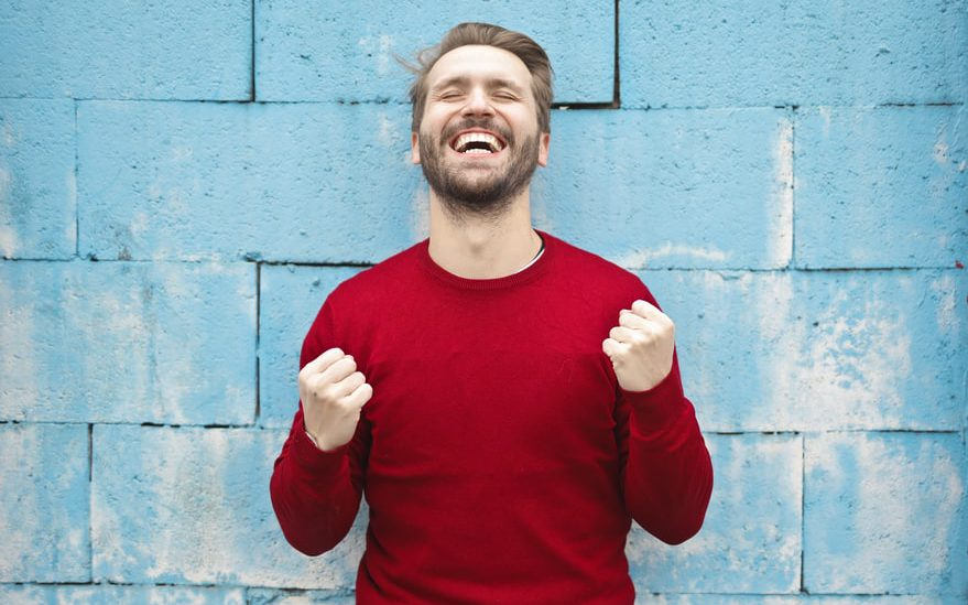 A man in read sweater standing against blue brick wall is happily clenching fists. The representation of a happy customer.