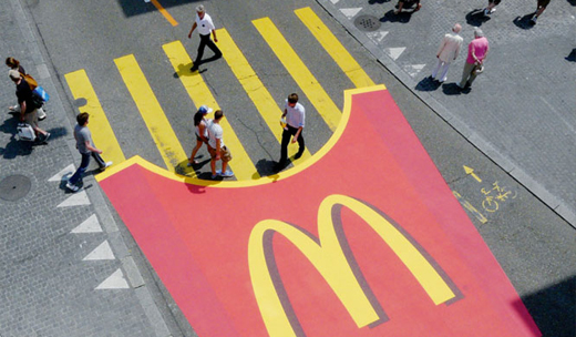 McDonald's fries box painted on the street. The fries are serving as a zebra crossing.