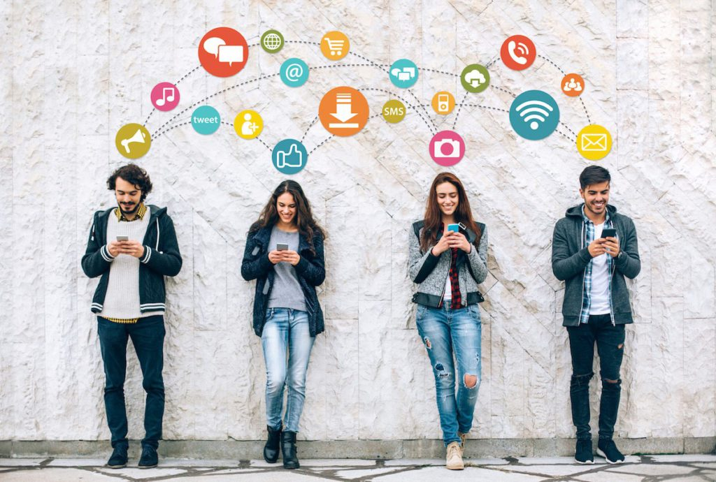 Four people standing against the wall and looking at their phones. The icons representing different activities on phone and social media are standing above them.