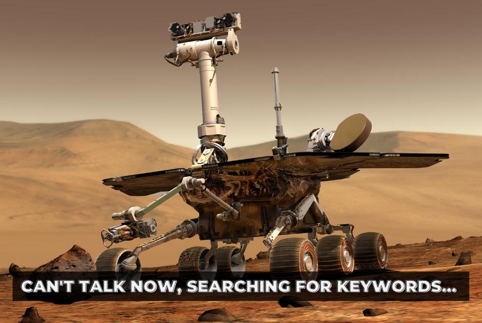 A robot on wheels drives through the desert. Text overlaid: