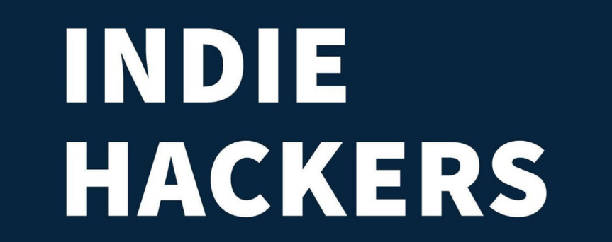 """White """"Indie Hackers"""" sign on a dark blue background"""