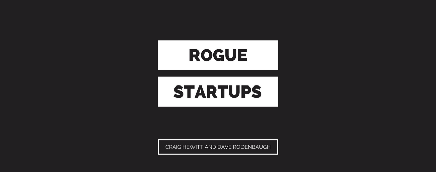 """Black background image with at the center two white rectangles with the black sign """"Rogue Startups"""""""