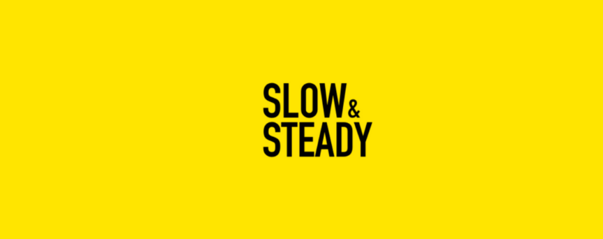 """Yellow background image with """"Slow & Steady"""" written in black at the center"""