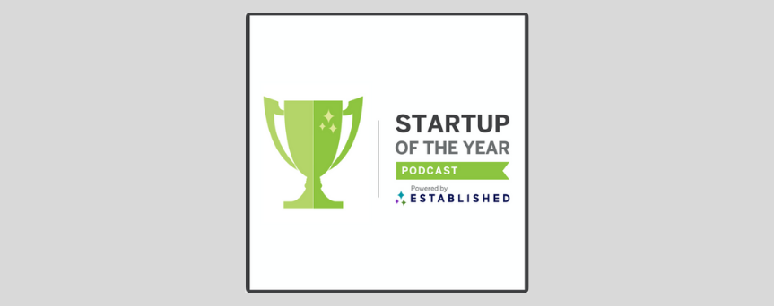 """White background image with black sign """"Startup of the Year Podcast"""". On the left, there' a green cup"""