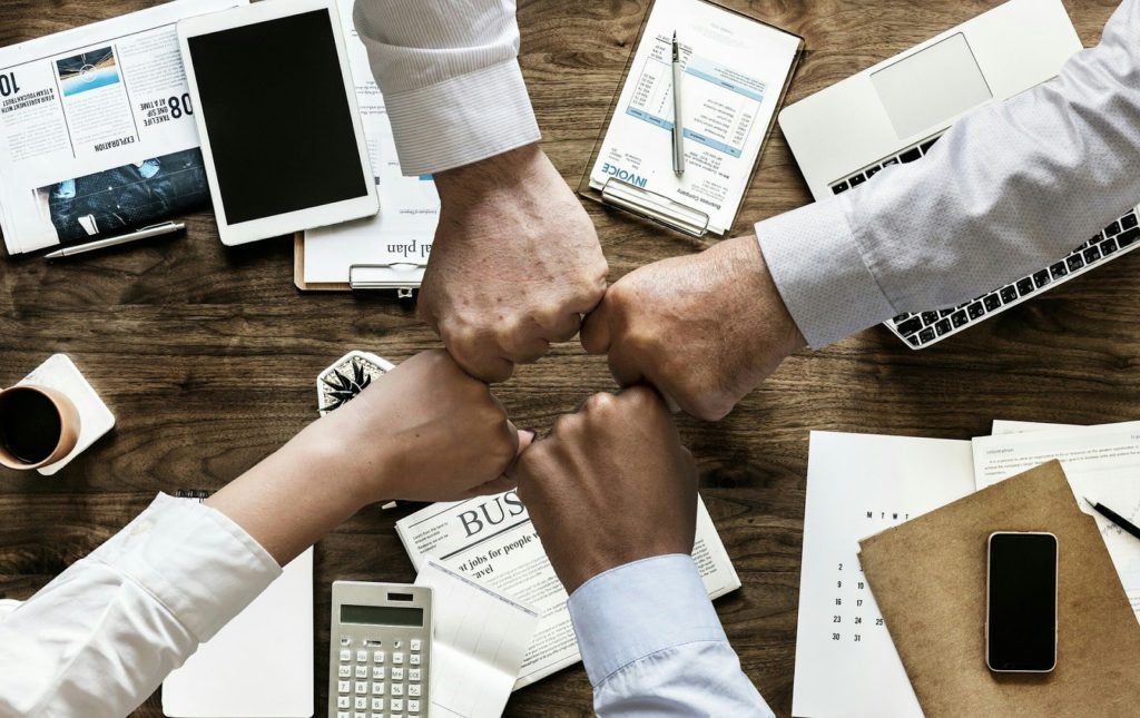 Four hands create a square together. Undere them, there are papers and office tools