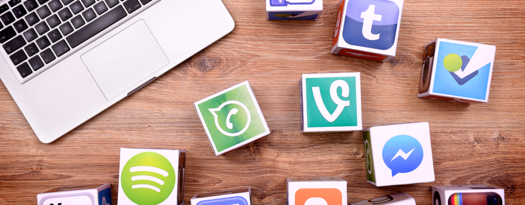 Infographic of social media logos next to a laptop standing on a desk