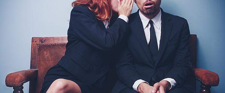 A man and woman in suits are sitting on a bench. The woman is whispering something controversial to the man's ear.