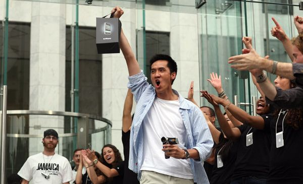A man standing in the crowd and holding a new phone. Representation of an early adopter.